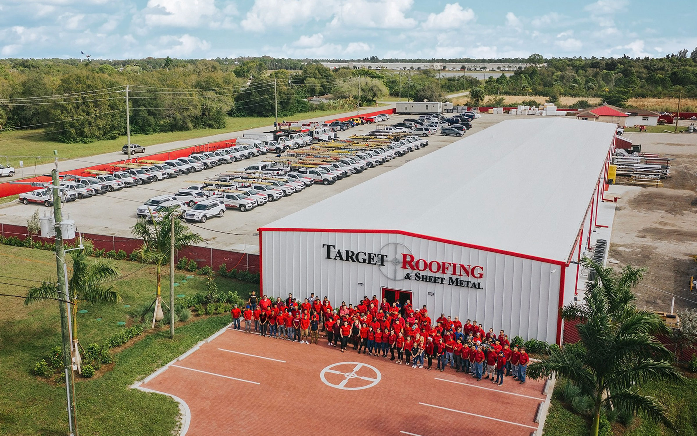 Target Roofing Drone Shot of Employees Standing in Front of Building