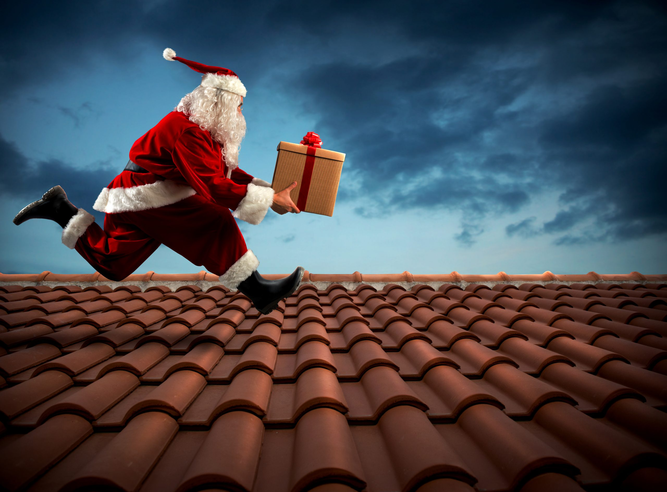 Santa Claus runs with a big present on a house roof